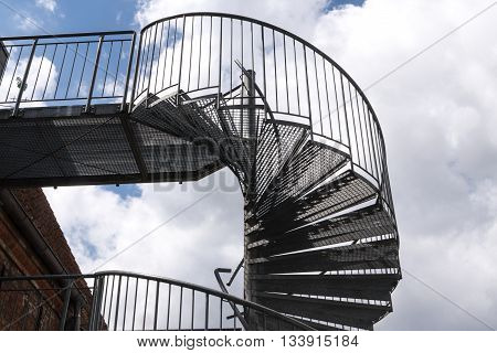 modern exterior spiral staircase from metal at an old building against a cloudy sky