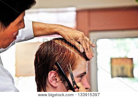young boy with red hair at the hairdresser