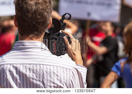 Filming street protest using video camera. Camera operator.