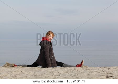 Young fitness girl a the beach in winter