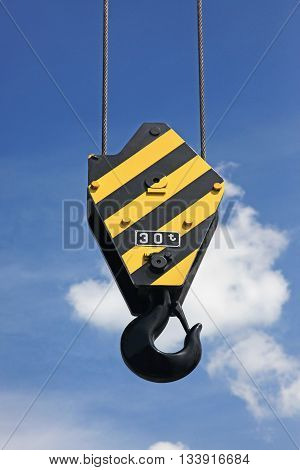 Crane hook with yellow and black stripes hanging blue sky in background