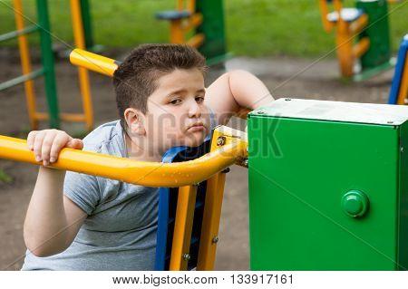 tired sad fat boy sitting on the sports simulator