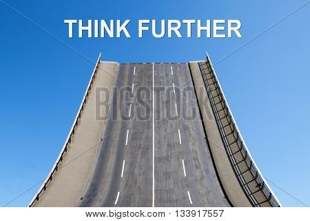 Road leads upwards in the blue sky text THINK FURTHER concept for innovation don't stop where the leaked paths ends