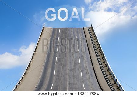 Road leads upwards in the blue sky with white clouds text GOAL business concept for new goals future and success