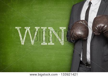 Win on blackboard with businessman wearing boxing gloves