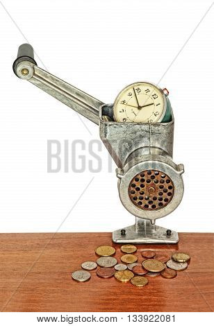 Money concept.Alarm clock in manual meat grinder and coins on wooden table.