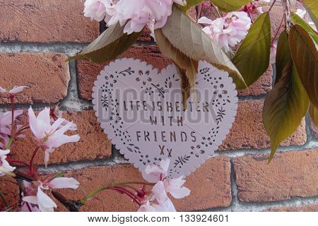 Heart shaped 'life is better with friends' plaque with a background of pink blossom