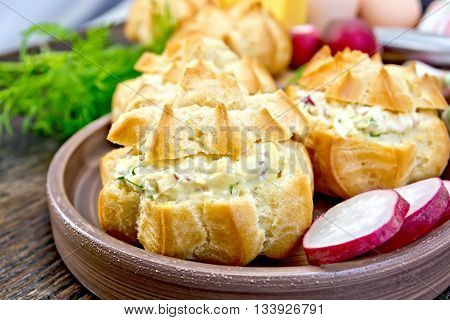 Appetizer of radish, dill, eggs and cheese in profiteroles on a clay plate, dill on a dark wooden board