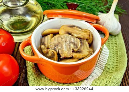 Champignons fried in a red ceramic pot on a napkin, garlic, dill and pomidoryna background dark wooden boards