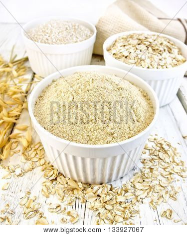 Meal oat, bran and oat flakes in three white bowls, oat stalks, towel on a background of wooden boards
