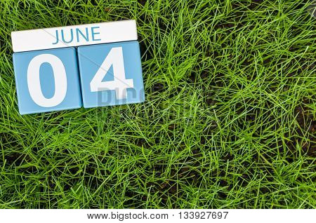 June 4th. Image of june 4 wooden color calendar on green lawn grass background. Summer day.