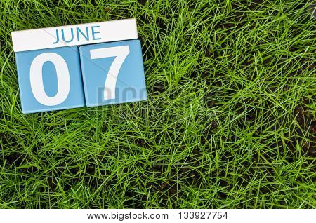 June 7th. Image of june 7 wooden color calendar on greengrass lawn background. Summer day, empty space for text.