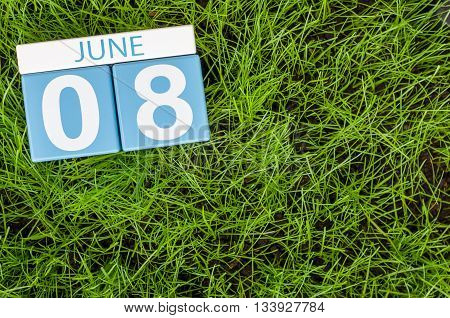 June 8th. Image of june 8 wooden color calendar on greengrass lawn background. Summer day, empty space for text.