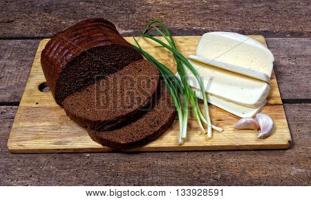 slised loaf of rye bread with cheese and spring onion closeup