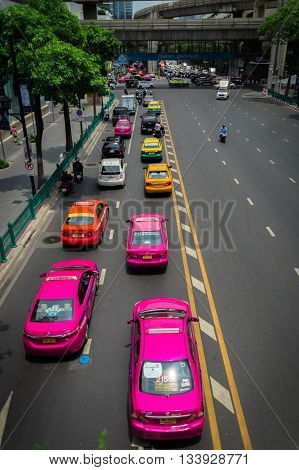 BANGKOK THAILAND - May, 2016: Famous pink and other colorful taxis queue in the Bangkok traffic.