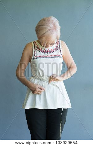 Senior lady checking waist measurement for weight loss