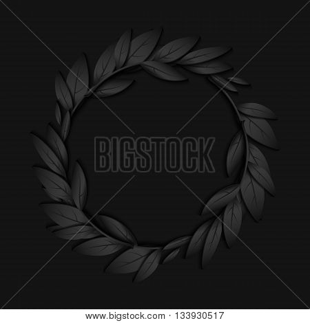 Circular frame of black paper branches and leaves jn black background.