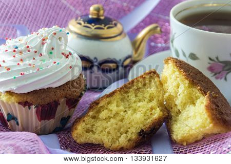 Split biscuit muffin and muffin, decorated with whipped protein cream, on the background cup of  tea  and teapot