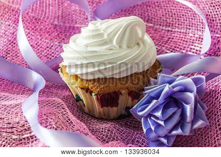 Tasty muffin cake with protein cream isolated on pink background