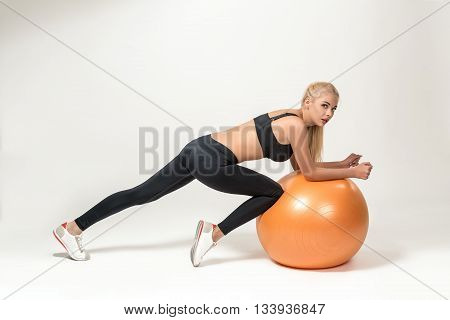 Young blonde woman training with fitball. she looks into the camera