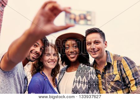 Four young casual friends having fun taking pictures at an urban celebration with a cityscape view in the evening