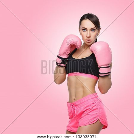 Beautiful sporty fit young woman in sportwear and pink boxing gloves. Isolated over pink background. Square composition. Copy space.