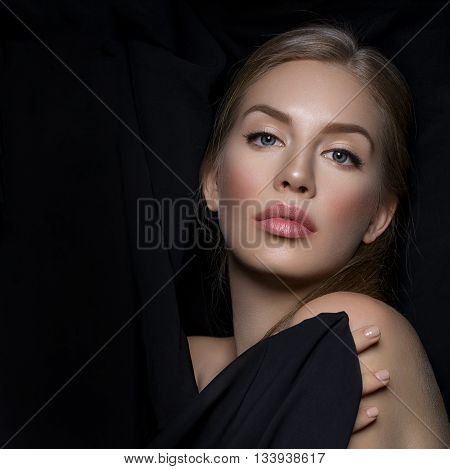 Beautiful young woman with blond hair and makeup covered with piece of black fabric. Beauty shot. Over black background. Copy space. Square composition.