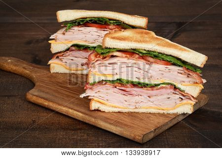 closeup toasted chicken club sandwich on wood cutting board