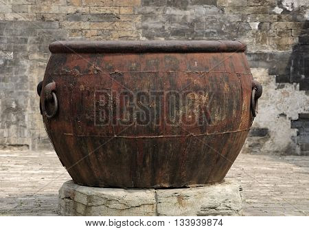 A large weathered and rusty metal urn within the forbidden city in Beijing China.