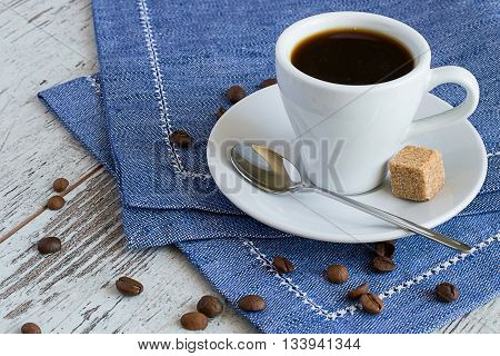 A cup of coffee, spoon, sugar cube and coffee beans on blue napkin on a light wooden background.