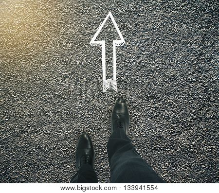 Guidance concept with businessman feet and arrow sketch showing direction on asphalt