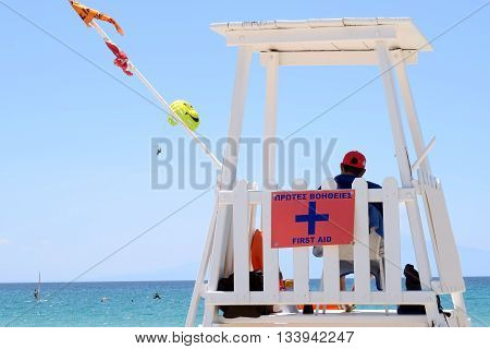 A lifeguard tower with a sign saying