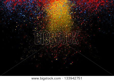 Freeze motion of colorful powder coming down isolated on dark black background. Abstract design of falling yellow blue and red dust. Particles cloud wallpaper.