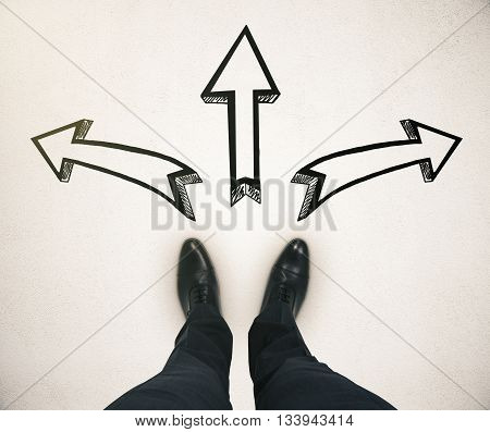 Different direction concept with businessman feet and arrow sketches on light ground
