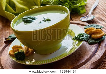 Healthy food: broccoli creamy soup in a green bowl on the wooden background.