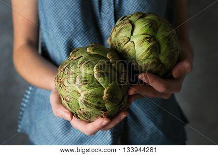 Woman holding few artichokes