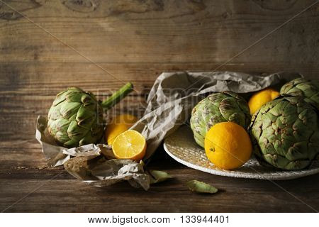 Artichoke with lemons on plate on wooden background