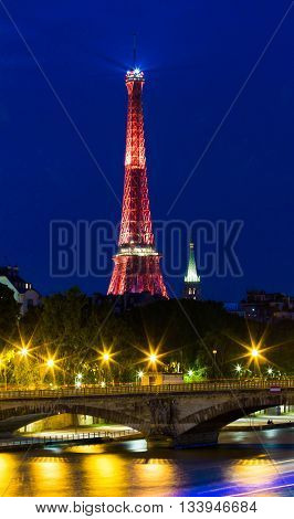paris; France-June 11 2016 : The Eiffel tower lit up in red color for soccer Europe championship 2016 in France. The Eiffel tower is one of the most visited monuments in the world.
