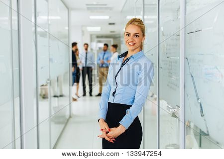 Young businesswoman with a smile posing in hallway