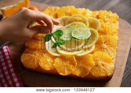 Female hand decorating citrus cake with fresh mint