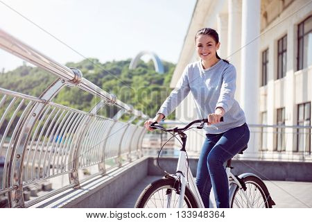Hey there. Cheerful young attractive woman having a rest after riding a bike on the quay in the city