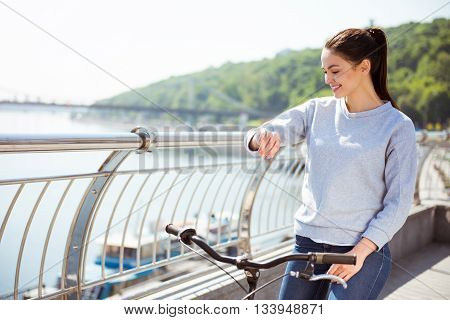 Hey I am on time. Delighted calm young woman looking at her watch while sitting on a bike and having a rest after riding