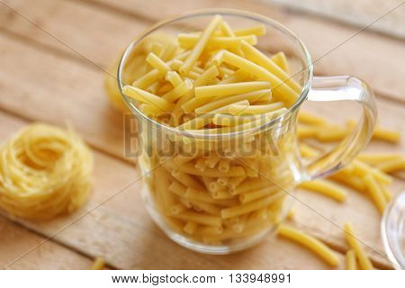 Macaroni in a glass cup on wooden table background