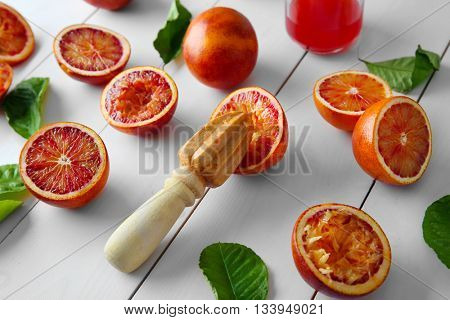 Juicing Sicilian oranges on white wooden table