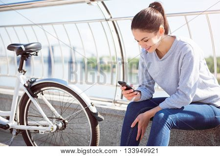 Lets look. Beautiful young woman looking at her phone while sitting near a bike and waiting for friends