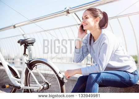 I am here. Smiling happy young woman talking on her smartphone while sitting near a bike