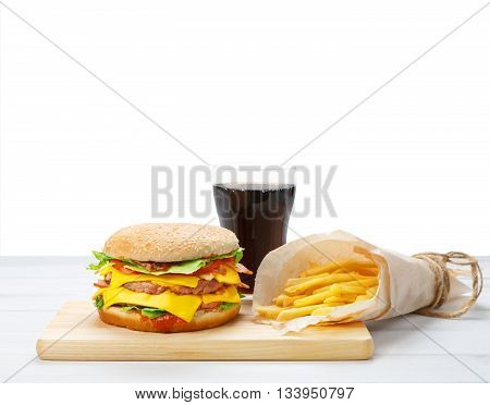 Fast food meal with copyspace. Hamburger, potato fries, cola drink. Takeaway food. Wrapped French fries packaging, Cola glass, double cheese burger at wood isolated. American food