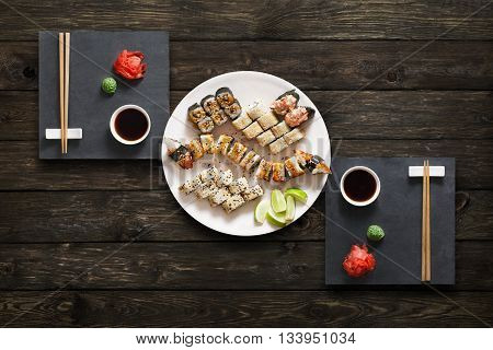 Japanese food restaurant, unagi sushi maki gunkan roll plate or platter set. Set for two with chopsticks, ginger, soy, wasabi. Sushi with eel at rustic wood background. Top view, flat lay.
