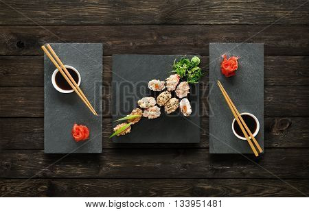 Japanese food restaurant, salmon sushi gunkan plate or platter set. Set for two with chopsticks, ginger, soy, wasabi. Sushi at black stone mat and rustic wood background. Top view, flat lay.
