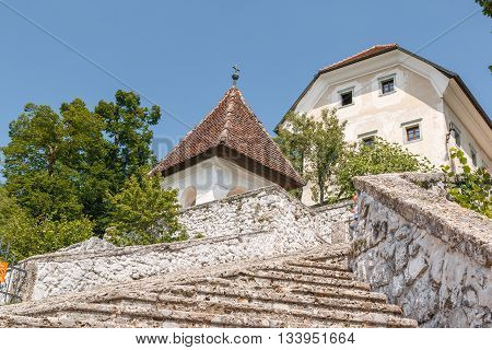 Photo shows white church on lake Bled Slovenia in summer.